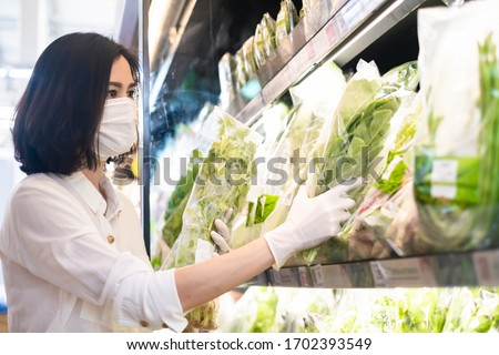 Asian woman wearing protect face mask and rubber gloves shopping food, fruit and vegetable in grocery department store. Girl choosing celery in supermarket during coronavirus crisis, covid19 outbreak.