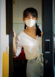asian woman wearing protection mask standing at open door