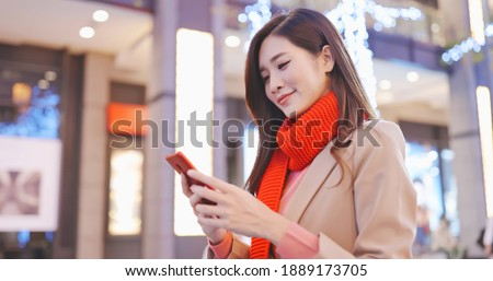 asian woman wearing scarf use smart phone and walk in the shopping street at night