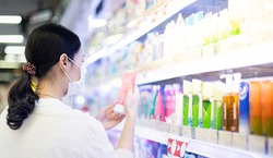 Asian woman wearing surgical mask and hand holding the bottle of facial foam for shopping in the aisle of the skincare department in supermarket, Due to the Covid-19 pandemic crisis.