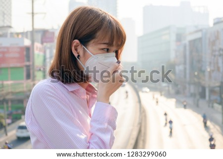 Asian woman wearing the N95 Respiratory Protection Mask against air pollution at road and traffic in Bangkok, healthcare concept