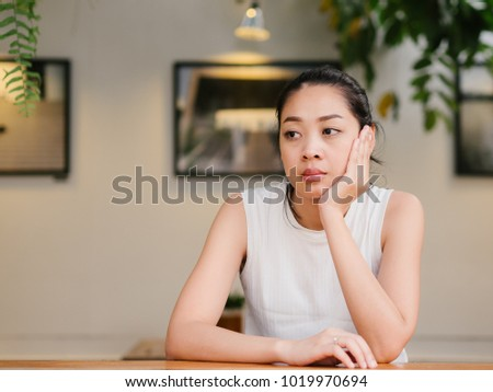 Asian woman with bored expression is waiting for some one or thinking of something. Foto d'archivio ©