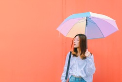 Asian woman with colorful umbrella on red wall background.