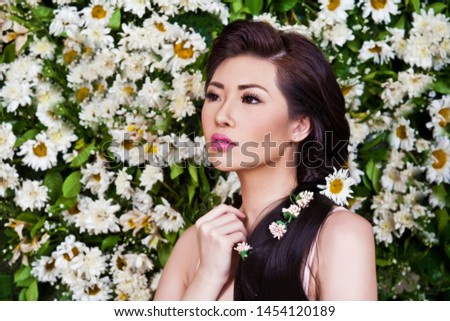 Asian woman with daisies in hair on the flower background