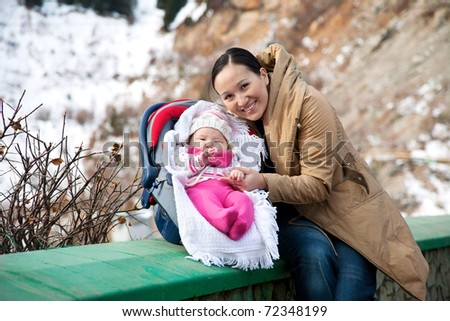 Asian woman with her baby in winter time