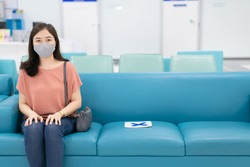 Asian woman with hygiene face mask standing in front of cashier counter in hospital close up with copyspace. Self protection during the COVID-19 or Coronavirus outbreak by using protective face mask.