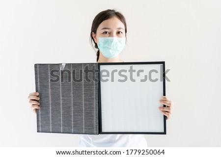 Asian woman with protective hygiene face mask changing a HEPA air purifier filter and showing up to compare between dirty used filter and the new filter. Woman replacing air filter close up.