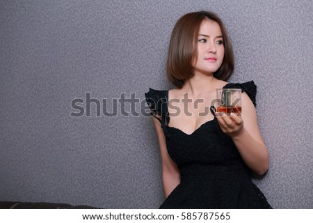 Asian woman with short hair, beautiful skin.Holding a glass of brandy only one.International Women's Day 2017. #585787565