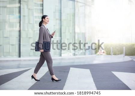 Asian woman with smartphone walking against street blurred building background, Fashion business photo of beautiful girl in casual suite with smart phone.