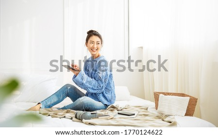 Asian woman with smile use tablet smartphone in blue winter sweater work home, Portrait beauty asia girl hygge relax in bedroom. Technology people connection digital online social media market banner