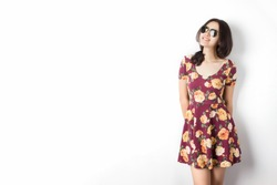 Asian woman with sunglasses and vintage flora dress standing by the wall.