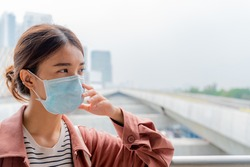 Asian woman with surgical mask face protection, Worried, scare, panicked, paranoid of pandemic.young girl in the skytrain background, Social distancing lifestyle, covid-19, medical, bangkok, thailand