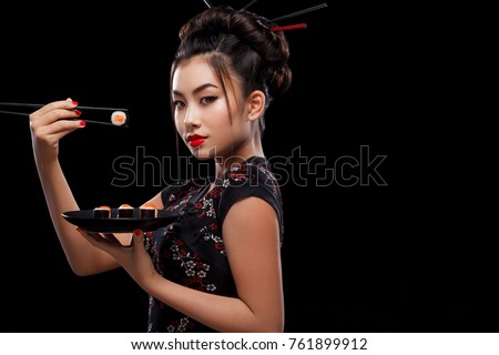 Asian woman with sushi eating sushi and rolls on a black background.