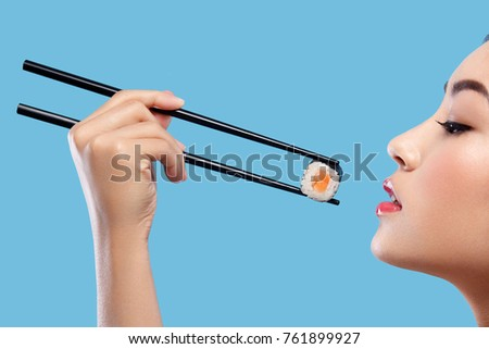 Asian woman with sushi eating sushi and rolls on a blue background. Black Friday sushi sale.