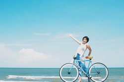 Asian woman with vintage bicycle in front of beautiful beach background