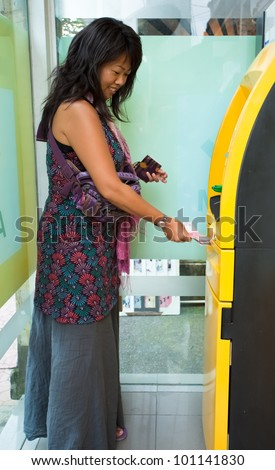 Asian woman withdrawing money at ATM