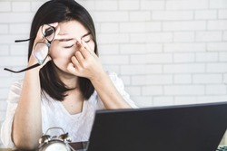 Asian woman worker suffering from eye strain taking off her eyeglasses tired from working on computer screen