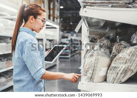 Asian woman worker working with digital tablet checking boxes Logistic import and export supplies packages in Warehouse , Logistics concept