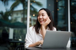 Asian woman working with computer laptop and drinking coffee in coffee shop cafe smile and happy face