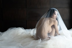 Asian woman wrapped in white fabric, beautiful slim.Naked woman art in white light transparent dress posing on a bed.