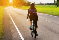 Asian women cycling on the road morning day - sport bike concept