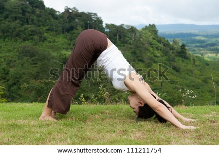 Asian women do Yoga with mountain view, Downward facing dog