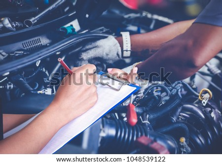 Asian women engineers and technicians are checking mechanic and inspecting on a car in auto repair shop the list on the board