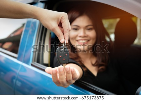 Asian women get car keys from seller's hands.