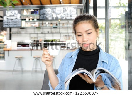 Asian women hold cup of coffee and reading magazine in coffee shop,Relax time in coffee shop