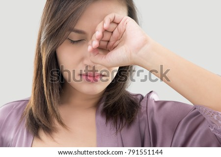 Asian women in purple robes have itching in the eye against gray background