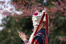 Asian women in tribal attire use communication technology to research wavelengths, travel, and contact online on holidays.