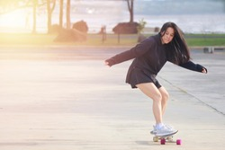 Asian women on skates board outdoors on beautiful summer day. Happy young women play surfskate at park on morning time. Sport activity lifestyle concept