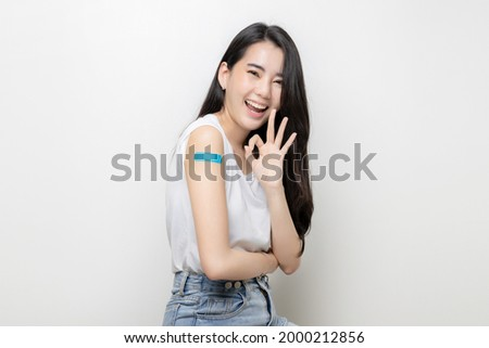 Asian Women Show Bandage On Arm. Happy Asian Woman Feels Good After Received Vaccine On White Background. Photo stock ©