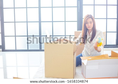 Asian women sit on computers and pack products according to customer orders