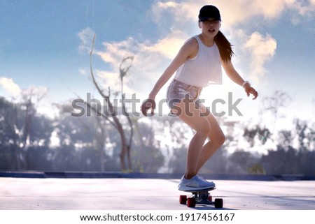 Asian women surf skate or skates board outdoors on beautiful summer day. Happy young women play surf skate at park on morning time. Сток-фото ©
