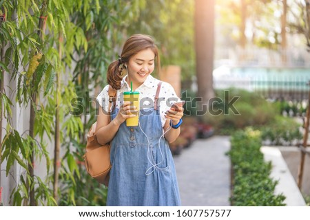 asian women tourist holding a yellow plastic cup listening to music on phone with earphones in, smiling in an urban district with nature district with sun shining and wearing a maternity and bag pack