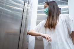 Asian women use elbows to press elevator button to avoid using hands.