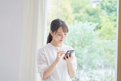 Asian women using the smartphone at home