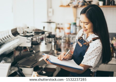 Asian women waiter hands on notebook, taking customer orders in restaurant or cafeteria, Thai girl coffee shop worker wearing apron write order serving for a client, writing food list service concept