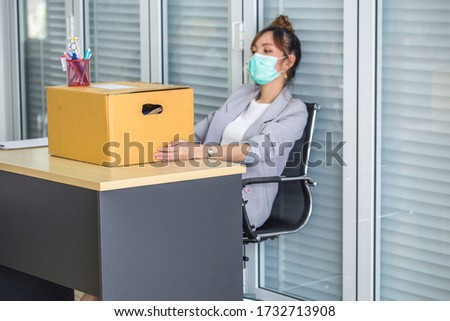 Asian women wear medical masks, store belongings after being laid off due to covid 19 disease Outbreak caused bankruptcy.Lay off and the economy concept. Stockfoto ©