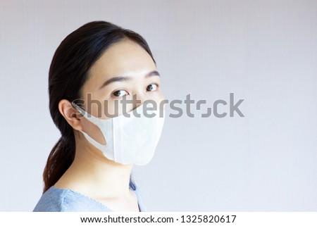 Asian women wearing a dust mask close up.