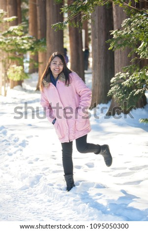Asian women wearing a pink overcoat stand in a beautiful garden with snow covered, expressing a refreshing, fun with smiling face.