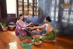 Asian women wearing Thai traditional dresses cooking Thai traditional food in the Thai ancient house Ayutthaya,Thailand