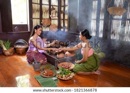 Asian women wearing Thai traditional dresses cooking Thai traditional food in the Thai ancient house Ayutthaya,Thailand