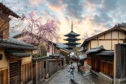 Asian women wearing traditional japanese kimono in Yasaka Pagoda and Sannen Zaka Street with Cherry blossom season in Kyoto, Japan. Woman walking to sight seeing in Japan.
