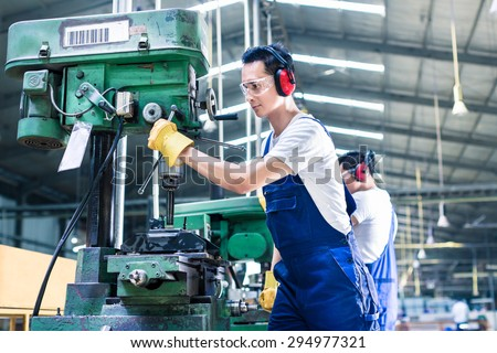 Asian worker in production plant drilling at machine on the factory floor #294977321