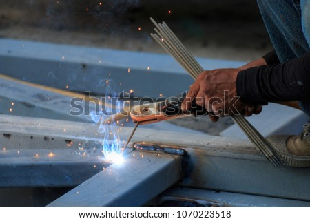 Asian worker making sparks while welding steel #1070223518