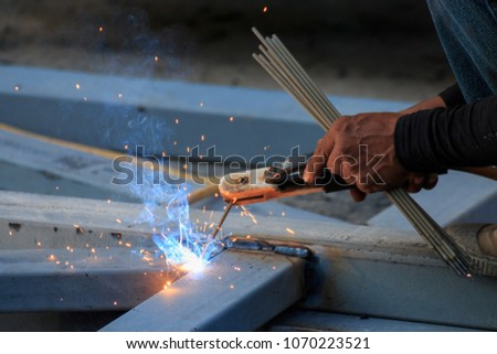 Asian worker making sparks while welding steel #1070223521