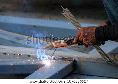 Asian worker making sparks while welding steel #1070223527