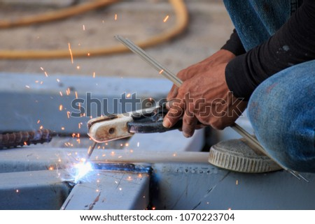 Asian worker making sparks while welding steel #1070223704